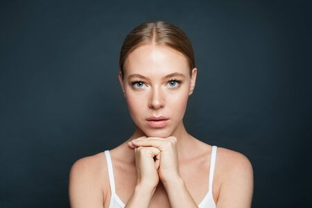 Perfect woman with clear skin on gray background 版權商用圖片