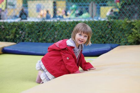 Little girl on playground in a park, jumping on trampoline. Little Girl seating on a Trampoline.