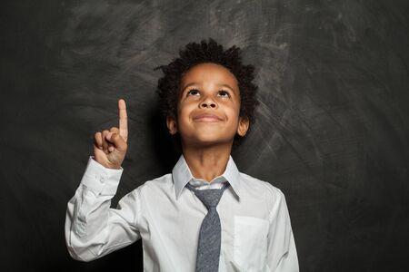 Kid little boy pointing up on black background
