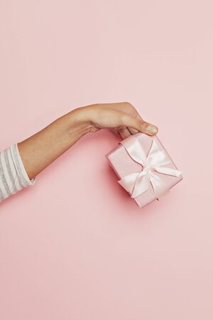 Gift in female hand on pink background. Abstract holiday present concept