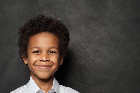 Happy child boy face on blackboard background