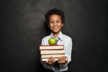 Happy black child student holding books and apple and smiling on chalkboard background 版權商用圖片 - 137823001