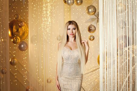Perfect young woman in golden evening gown. Fashion model with long blonde hair