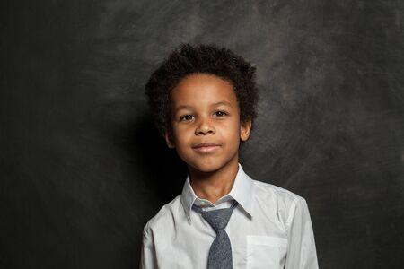 Happy black kid school boy. Smart child on blackboard background portrait