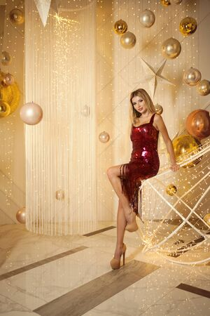Fashionable woman posing against golden party background