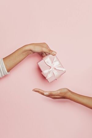Perfect pink gift and two female hands on pink background for birthday card, Xmas, mothers day and wedding 版權商用圖片