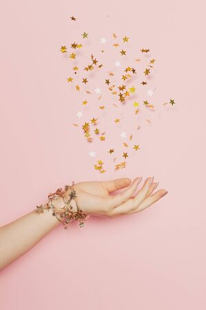 Celebration, wedding and birthday party concept. Gold confetti stars blowing up in female hand on pastel pink background