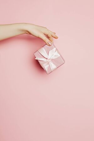 Female hand giving pink gift box with silky ribbon and bow on pink background