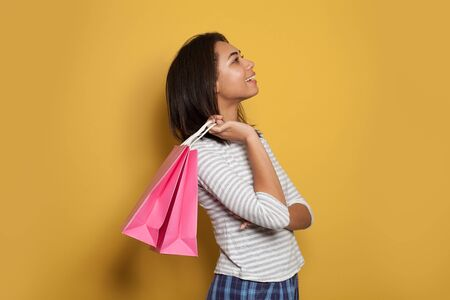 Young happy woman holding pink shopping bags on yellow background