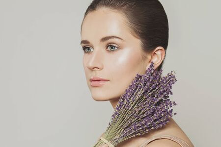Nice woman with clear skin and lavender flowers close up portrait 版權商用圖片