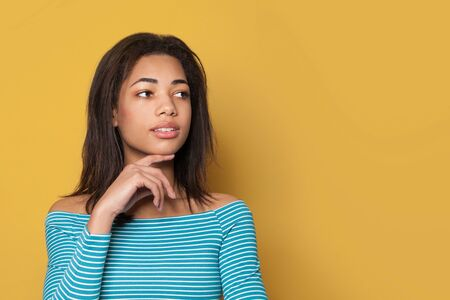 Indoor portrait of african American woman looking aside on yellow background