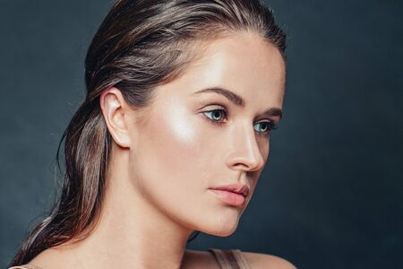 Elegant woman portrait. Beautiful face with healthy clear skin on dark background