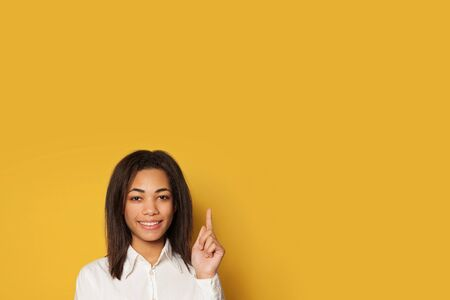 Young smiling American woman pointing up on yellow background with copy space