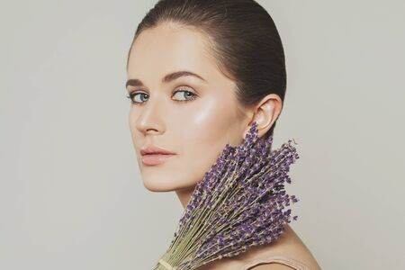 Attractive female face close up and lavender flowers