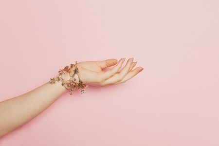 Young woman hand on pink background. Woman hand holding presenting