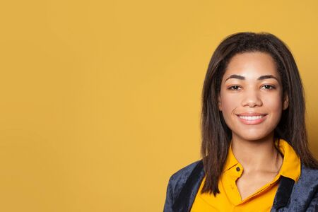 Young African American woman on yellow background