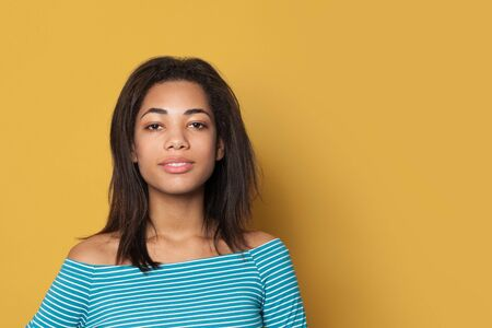 Beautiful African American woman on yellow background