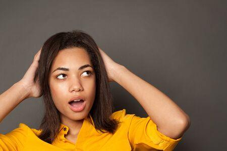 Shocked black woman on gray background 版權商用圖片