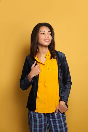Portrait of young black woman student on yellow background