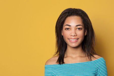 Smiling black woman on yellow studio background