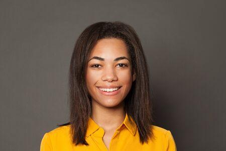 Smart black girl student smiling on gray background