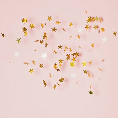 Golden confetti blowing on pink background