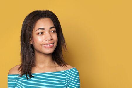Happy cheerful brunette girl on yellow background