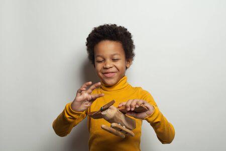 Happy black kid boy playing plane model on white background
