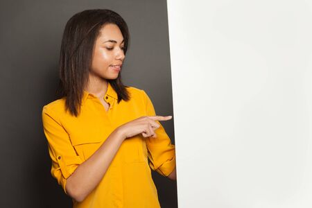 African American woman pointing at white empty signboard on gray background 版權商用圖片
