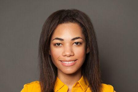 Pretty positive black woman smiling, cute female face close up portrait