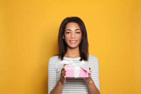 Nice black woman opening pink gift box with white silky ribbon on bright yellow background 版權商用圖片