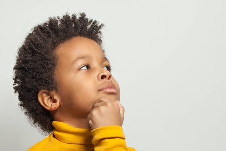 Little clever curious black child boy thinking on white background, close up portrait