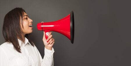 Young woman speaks by red loudspeaker on gray background