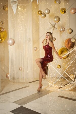 Beautiful girl in red dress on golden party background Imagens