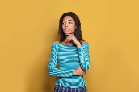 Thinking black woman looking aside on yellow background