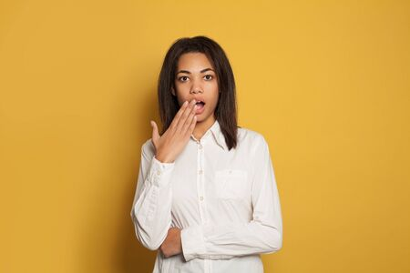 Surprised woman with black skin on yellow background