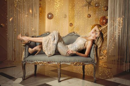 Beautiful woman fashion model on luxurious vintage sofa on golden background 版權商用圖片