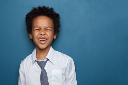 Little black child boy smiling and looking up on blue background