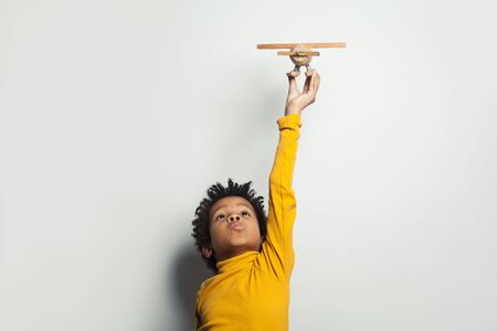 Little black child boy playing plane model on white background