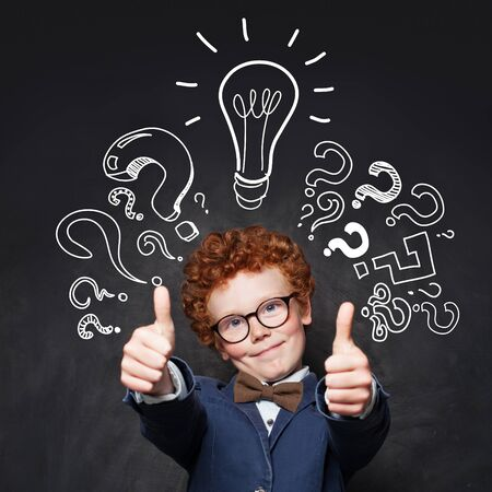 Child 9 years old having fun and showing thumb up on blackboard background with lightbulb