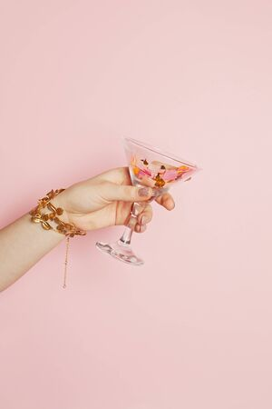 Birthday holiday concept. Female hands showing wine glasses with gold confetti sparkle on pink background 版權商用圖片