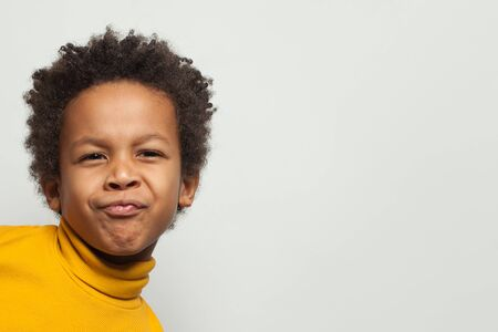 Funny black child boy grimacing on white background