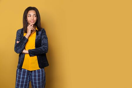 Smart black woman student thinking on yellow background with copy space