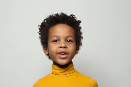 Happy black child boy in yellow turtleneck sweater smiling on white background