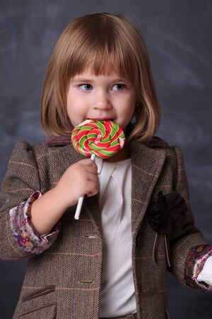 Little girl hold a colorfull lollipop. Little child with sweet lollipop. Happy candy girl. Enjoying.