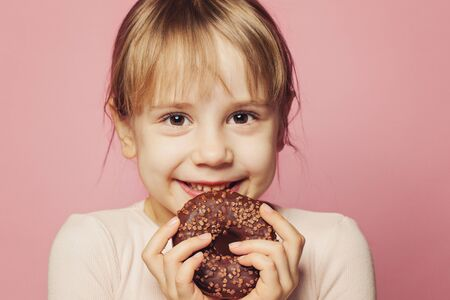 Happy little girl holding chocolate donut on pink background