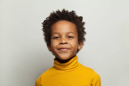 Handsome black child boy smiling and looking at camera on white background