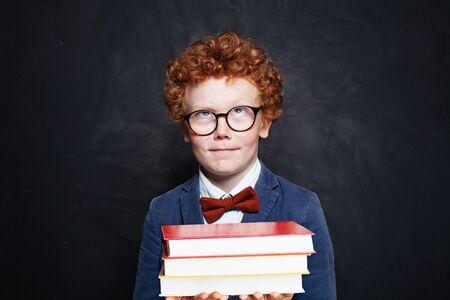 Little smart child in blue student uniform holding books on blackboard background 版權商用圖片