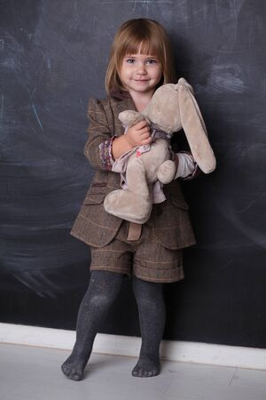 Cute Happy little girl hugging her toy rabbit