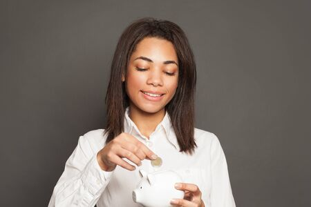 Pretty positive black woman putting coin in piggy bank